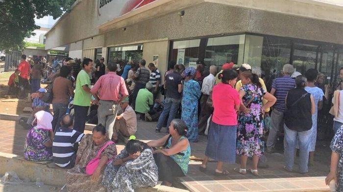 Adultos mayores esperan en la puerta del banco el cobro de su pensión