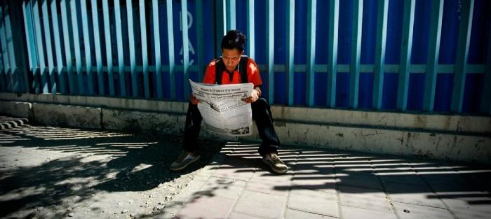 Un joven timorense lee el periódico | Foto: UN/Martine Perret